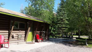 cabin-exterior-with-green-door-red-chairs-300x169.jpg